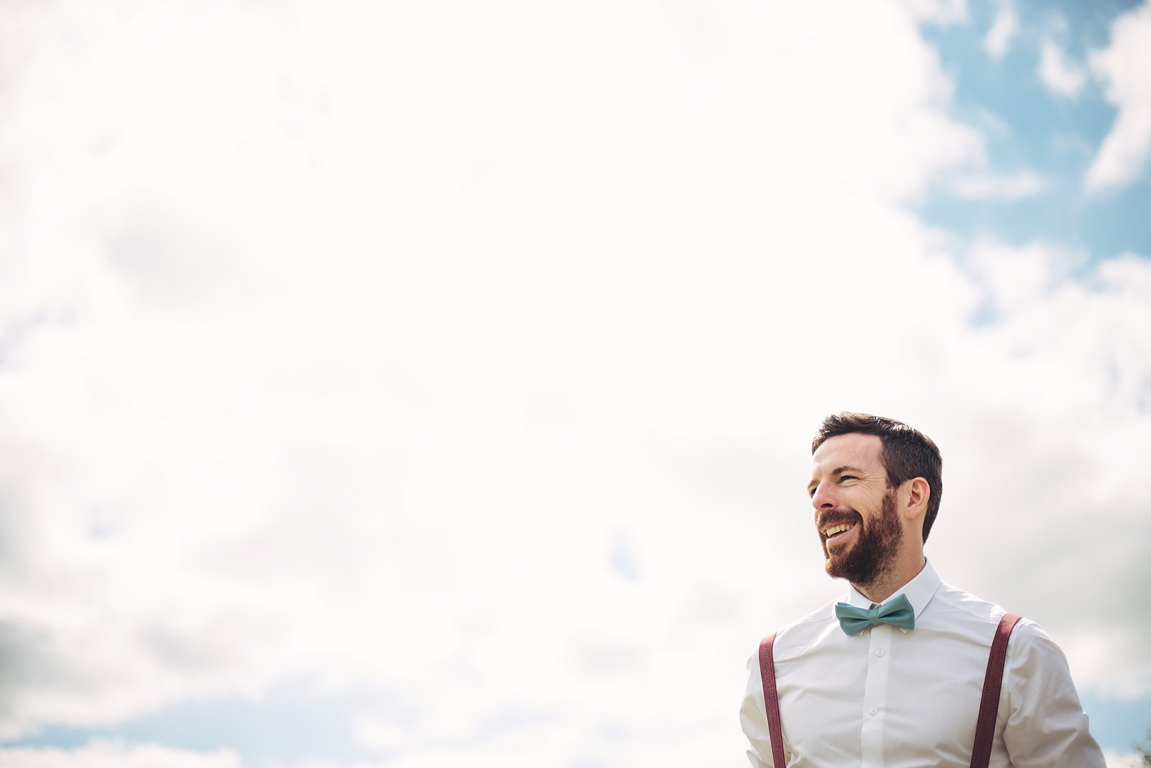 A man a groom at his wedding set against the sky