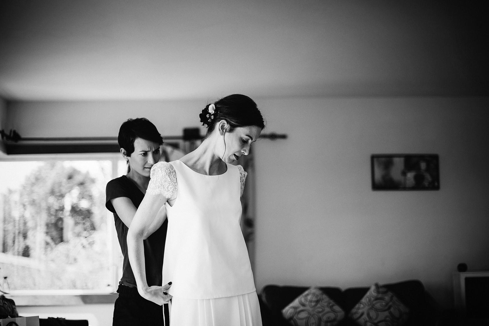 Bridesmaids fixing the brides dress