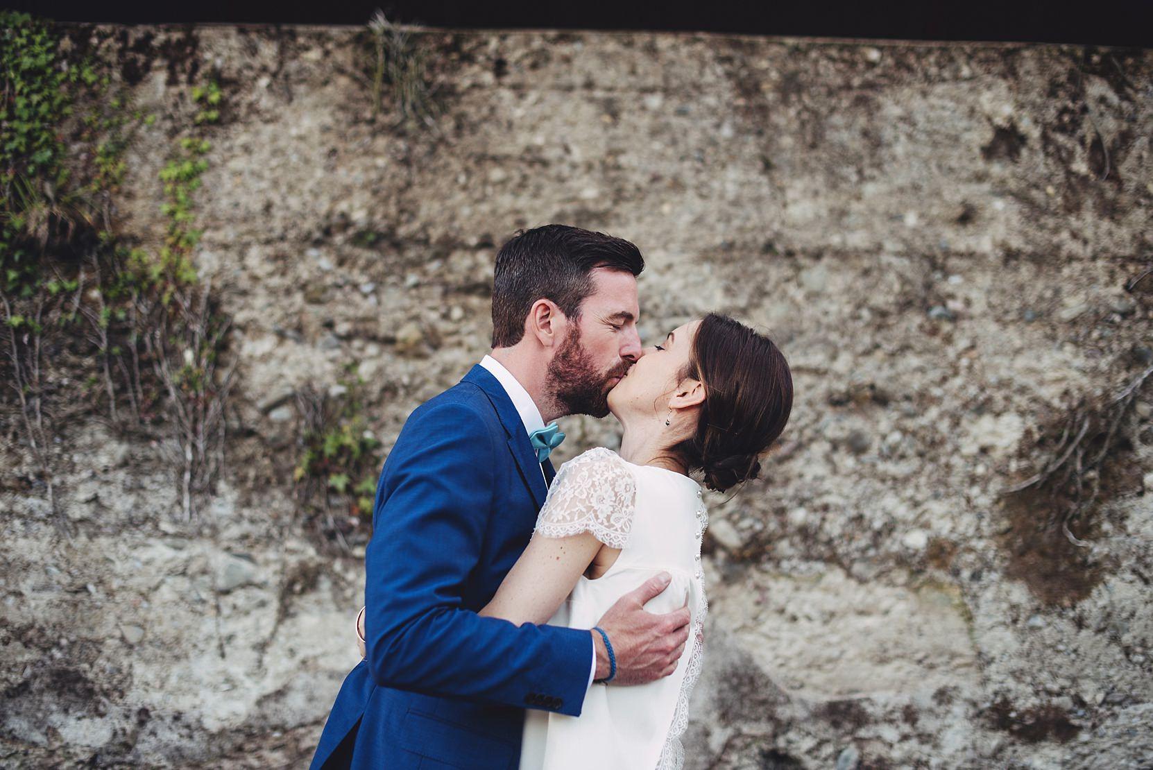 Bride and groom kissing at a wall at a wedding