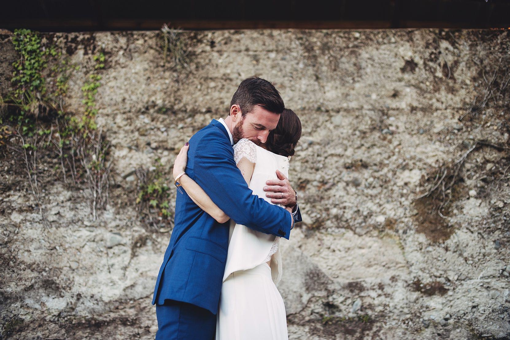 Bride and groom hugging at a wall at a wedding