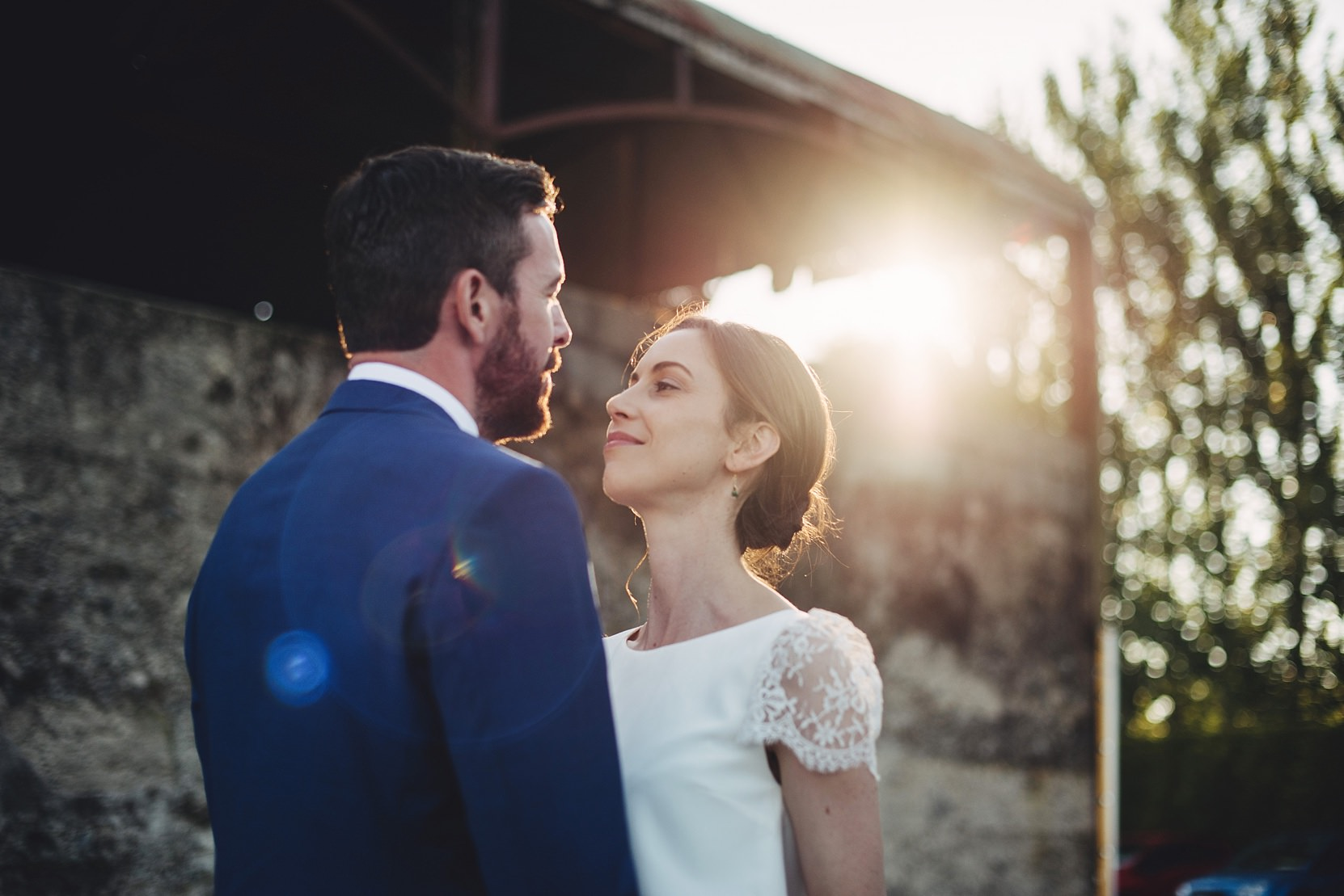Bride and groom standing at a wall in beautiful light at a wedding