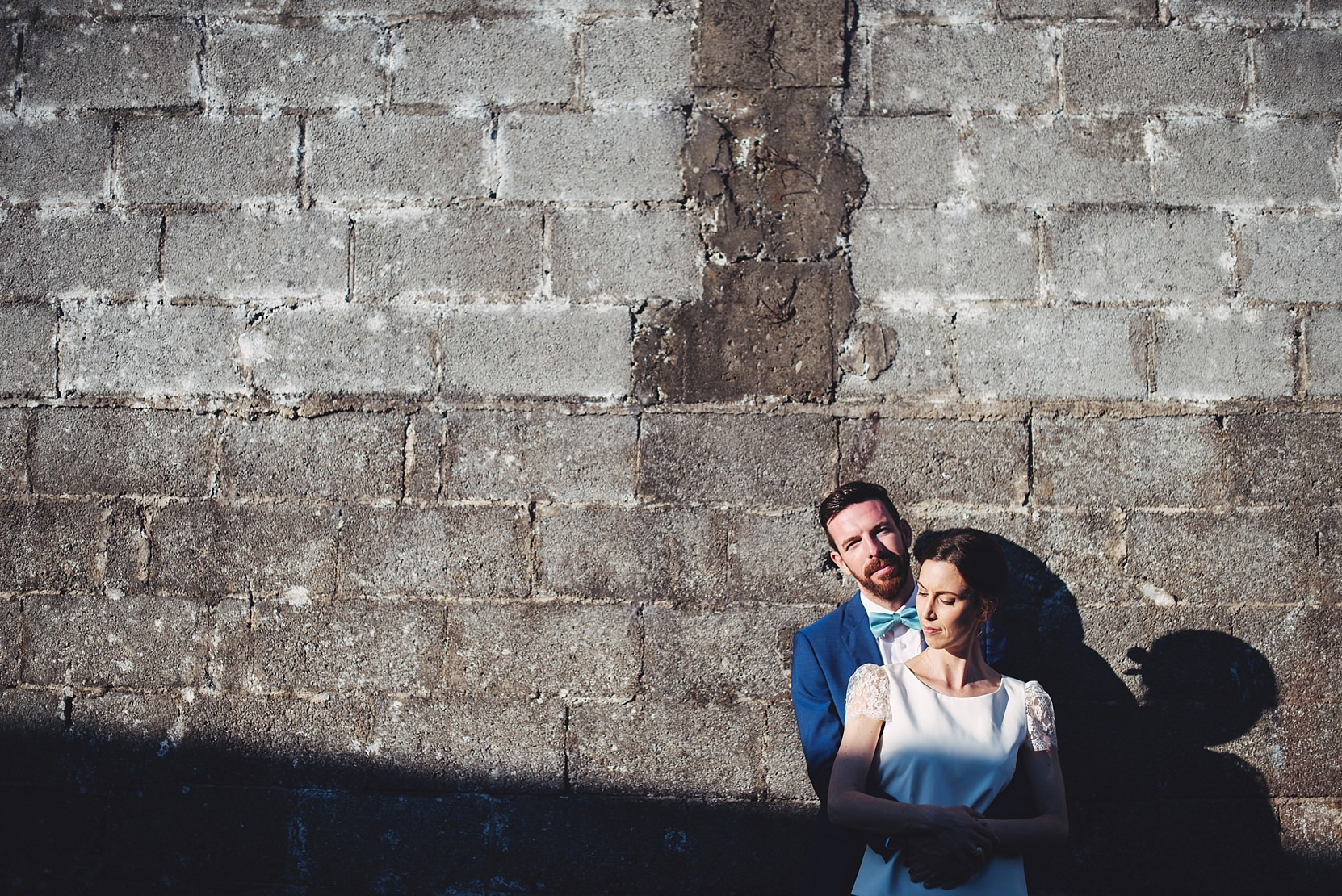Bride and groom standing at a wall at a wedding in good light