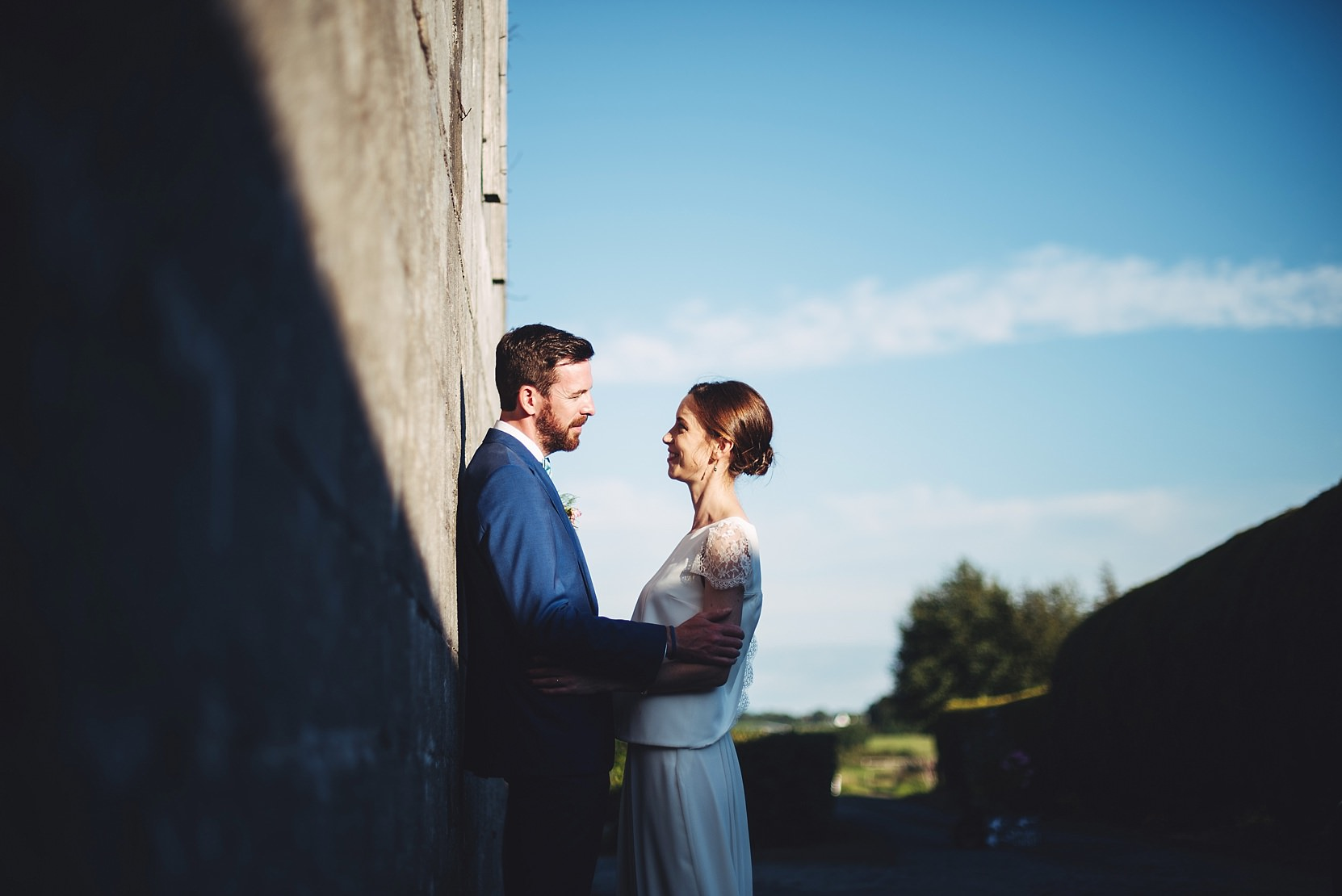 Bride and groom standing at a wall at a wedding in good light with the sky in the background