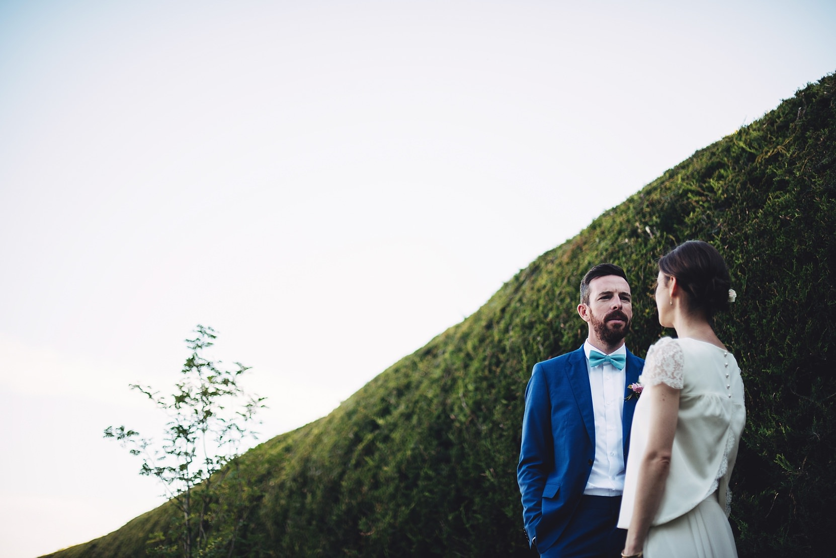 Bride and Groom standing at a nice hedge at their wedding