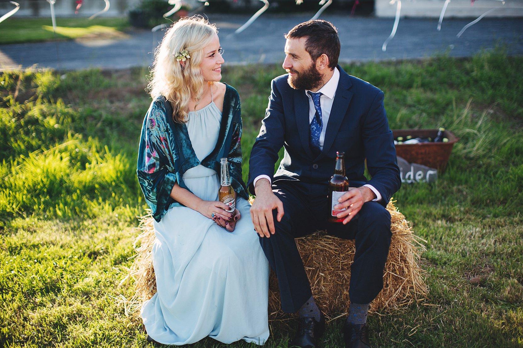 Guests sitting on hay-bales at a DIY wedding