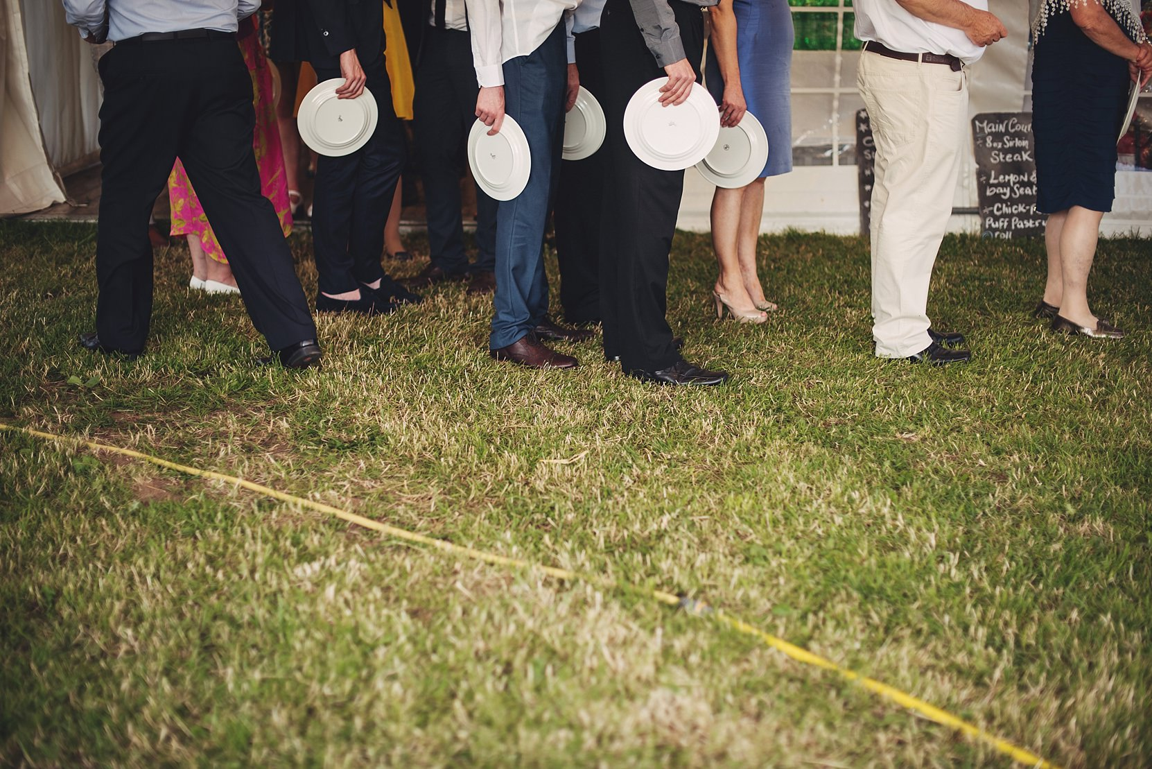 Guests queuing up for food at a wedding holding plates