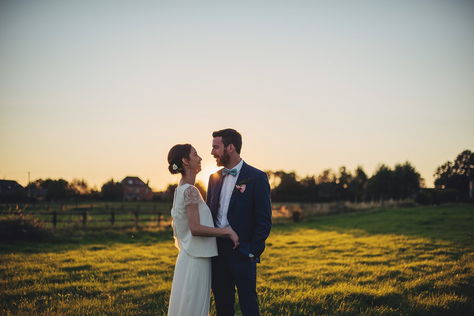 Bride and Groom standing in a beautiful field at sunset on a farm in Limerick