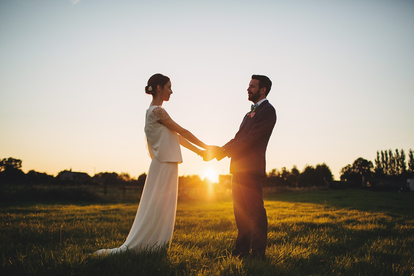 Beautiful shots of a bride and groom at sunset in a field