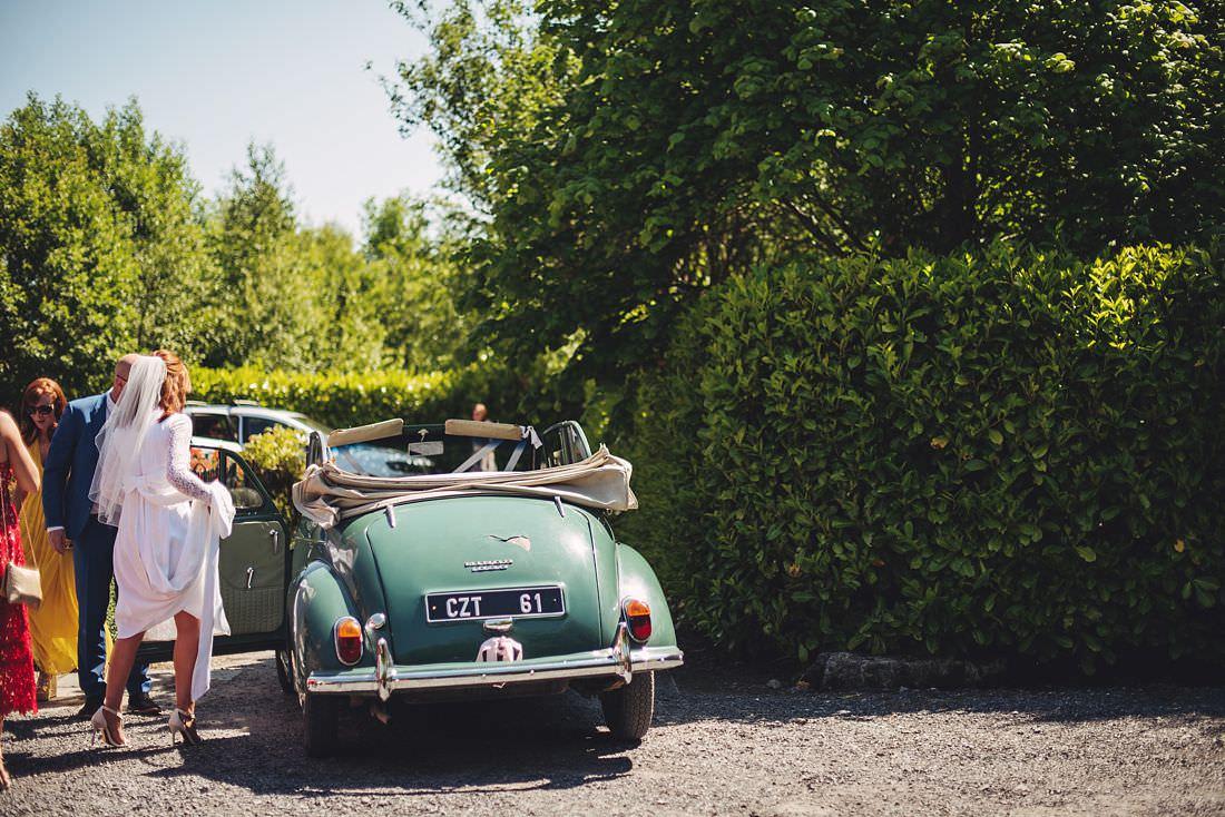 Bride in classic wedding car