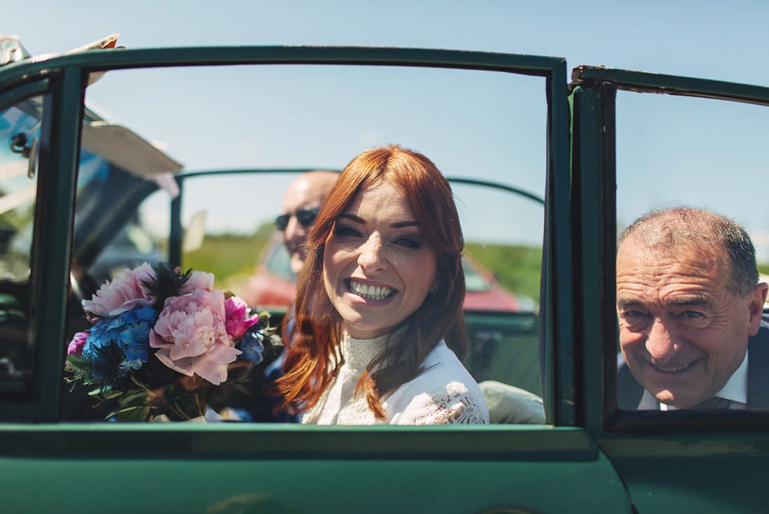 Bride smiling in Vintage car